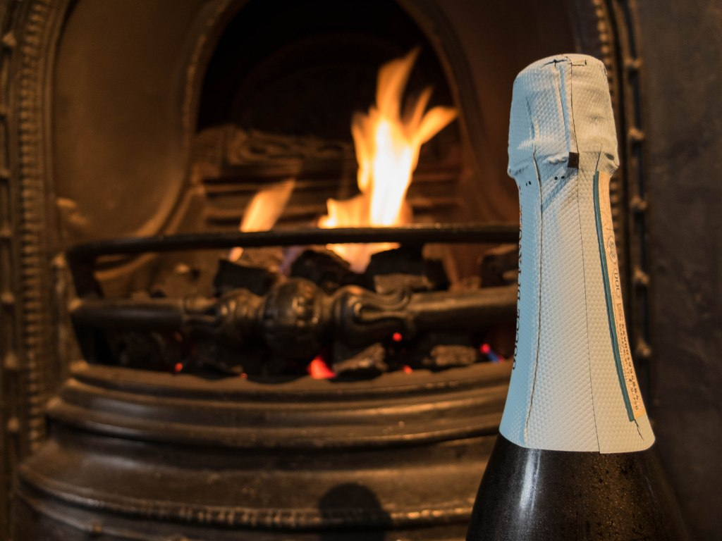 The neck of a bottle of prosecco in front of a fire.